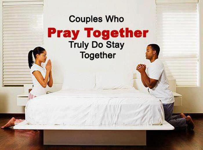 A male and a female kneeling on either side of a bed with white sheets facing each other they are definately finding times to pray
